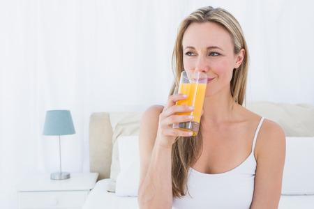 tomando jugo: Blonde sonriente vaso de jugo de naranja en el pa�s en el dormitorio