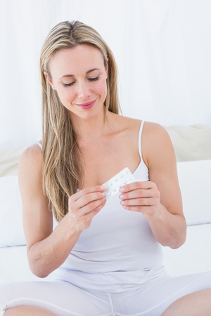 dependent: Smiling blonde woman with her pills on bed at home in the bedroom Stock Photo