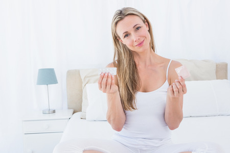 Smiling woman holding the pill and condom at home in the bedroom Stock Photo