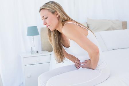 dolor de estomago: Sufrimiento rubia bonita con dolor de est�mago como en casa en el dormitorio
