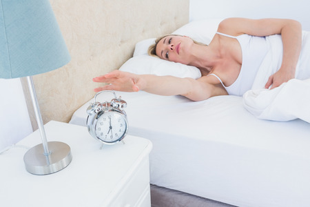 turning table: Blonde woman lying in bed reaching for alarm clock at home in the bedroom