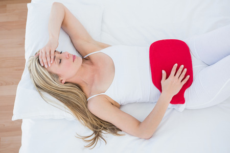 Woman using hot water bottle for her stomach pain at home in the bedroom Stock Photo
