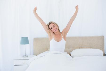 stretching: Mujer rubia Pacífica extiende en la cama en su casa en el dormitorio