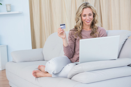 lifestyle caucasian: Happy blonde sitting on couch shopping online at home in the living room