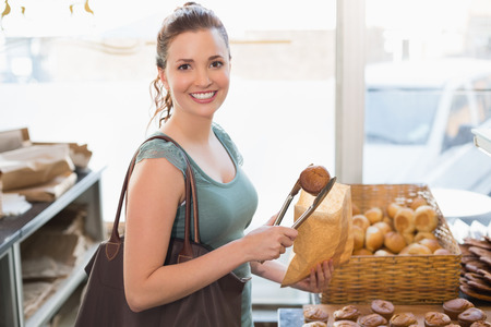 Pretty brunette picking out croissant at the bakery photo