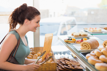 swiss roll: Pretty brunette looking at swiss roll at the bakery Stock Photo