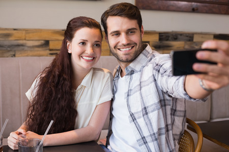 Cute couple on a date taking a selfie at the cafe photo