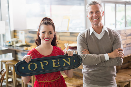 small business team: Cafe owners smiling at the camera at the cafe Stock Photo