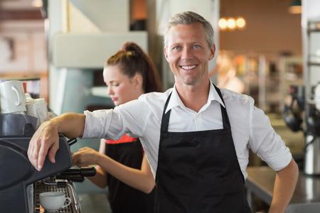 Barista lachend naar de camera in het cafe
