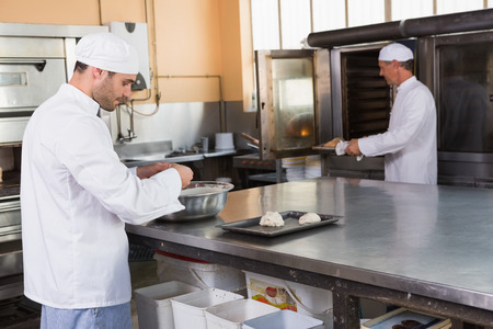 Baker making dough in mixing bowl in the kitchen of the bakery photo