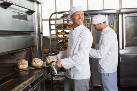 industrial kitchen: Happy baker holding tray of fresh bread in the kitchen of the bakery Stock Photo