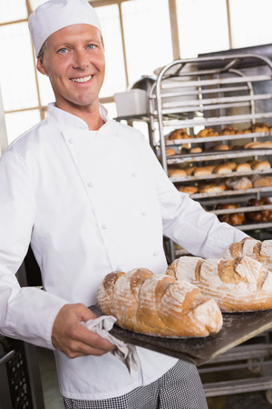 bakery store: Baker holding tray of bread in the kitchen of the bakery