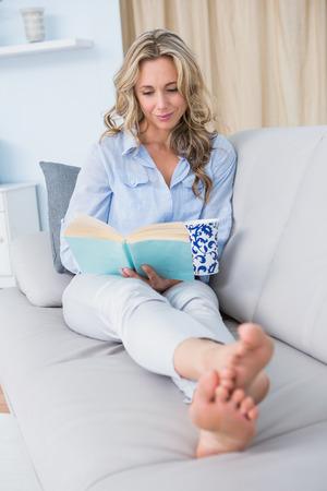 femme blonde: D�tendu blonde assise sur le canap� en lisant un livre � la maison dans le salon Banque d'images