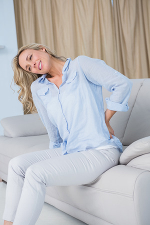 wincing: Grimacing blonde getting back pain at home in the living room