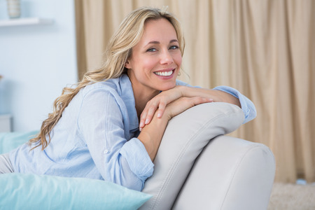 Cheerful pretty blonde sitting on couch at home in the living room Stockfoto