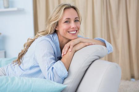 Vrolijke mooie blonde zittend op de bank thuis in de woonkamer