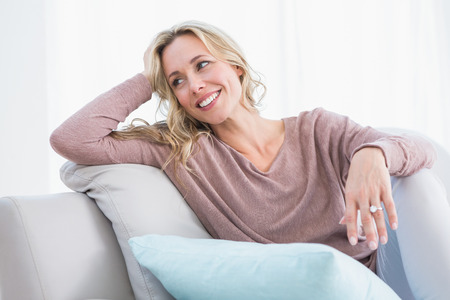 Blonde sitting on couch smiling and thinking at home in the living room