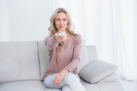 changing channel: Smiling blonde on couch changing tv channel at home in the living room Stock Photo