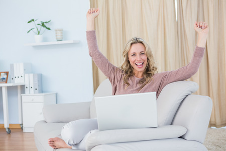 household money: Smiling blonde cheering and using laptop at home in the living room