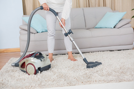 vacuum: Woman using vacuum cleaner on rug at home in the living room