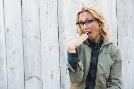 gesturing: Shocked blonde in glasses gesturing against bleached wooden planks