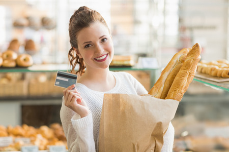 fresh bakery: Pretty brunette with bag of bread and credit card at the bakery
