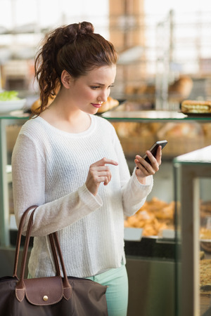 fresh bakery: Pretty brunette sending a text at the bakery Stock Photo