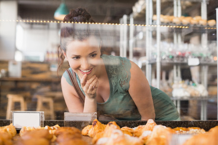 Jolie brunette regardant pastrys à la boulangerie