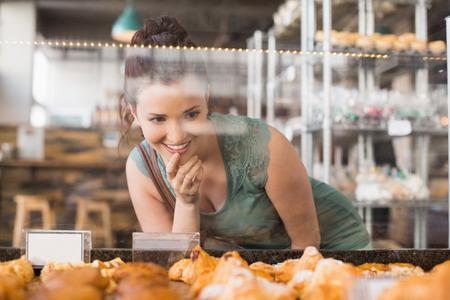 Pretty brunette kijken naar gebak in de bakkerij