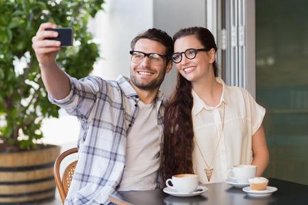casal: Casal bonito em uma data tomar um selfie no café Imagens
