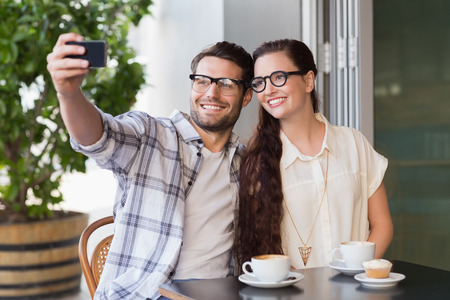 man with glasses: Cute couple on a date taking a selfie at the cafe