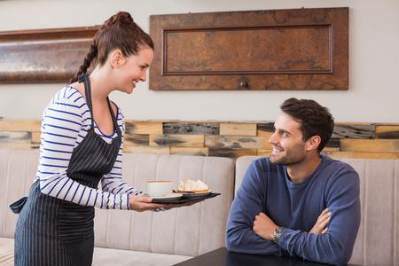 bringing: Waitress bringing man coffee and tart at the cafe