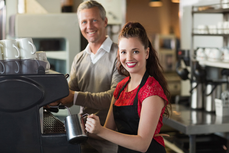 male teenager: Barista making a cup of coffee at the cafe