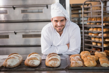 panadero: Panadero feliz de pie cerca de la bandeja con pan en la panadería