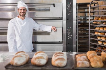 haciendo pan: Panadero feliz apoyándose en horno profesional en la panadería