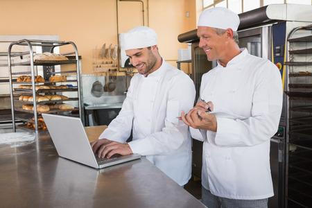 パン屋パン屋のキッチンでのラップトップに取り組んで一緒に笑みを浮かべてください。
