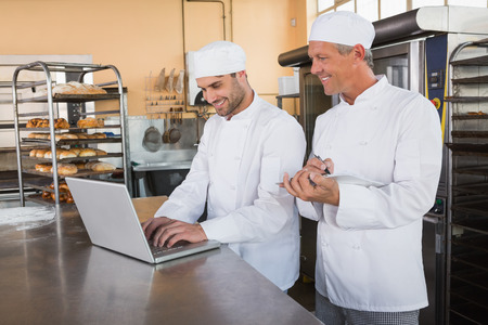 bakery store: Smiling bakers working together on laptop in the kitchen of the bakery
