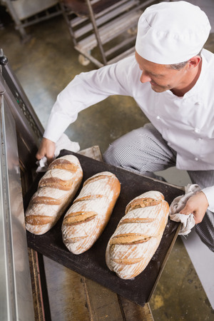 Baker taking tray of fresh bread out of oven in the kitchen of the bakery Stock fotó