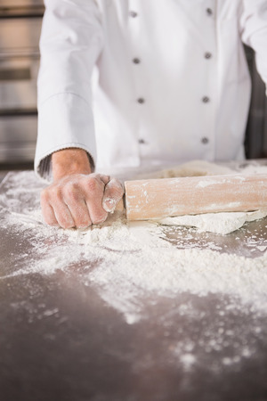Close up of baker using a rolling pin in the kitchen of the bakery