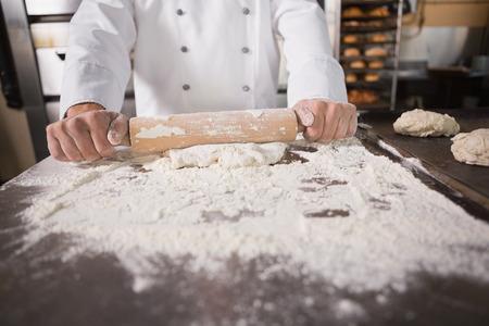 panadero: Cierre de panadero con un rodillo en la cocina de la panader�a Foto de archivo