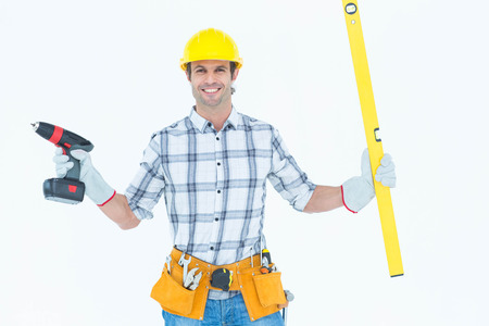 Portrait of confident technician holding portable drill and spirit level over white background photo
