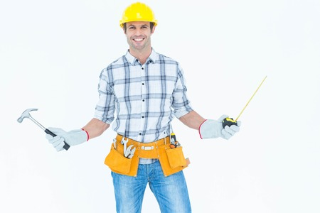 Portrait of confident technician holding hammer and measure tape over white background photo