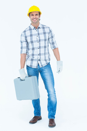 Portrait of happy male technician carrying tool box over white background photo