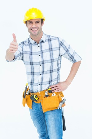 Portrait of happy handyman gesturing thumbs up sign over white background photo