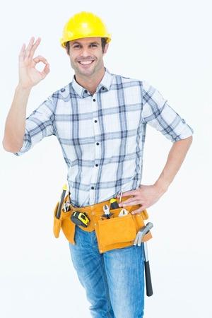 Portrait of happy handyman gesturing OK sign over white background photo