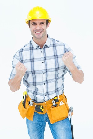 Portrait of successful technician celebrating victory over white background photo