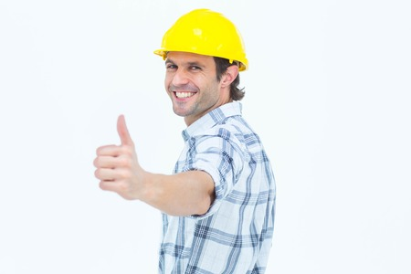 Portrait of happy technician gesturing thumbs up over white background photo