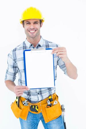 Portrait of confident carpenter holding clip board over white background photo