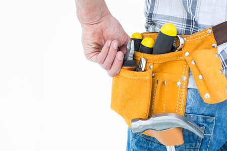 waist belt: Cropped image of technician with tool belt around waist over white background