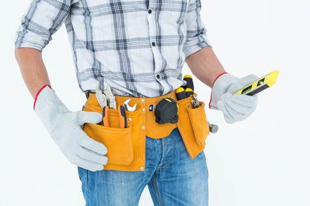 Cropped image of technician holding spirit level over white background photo